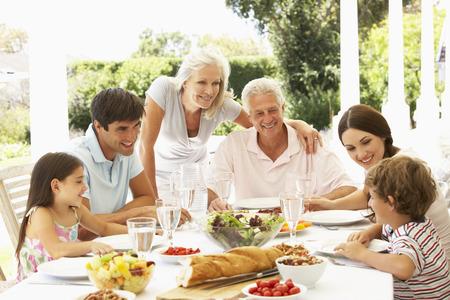 Familia que come el almuerzo al aire libre en el jardín