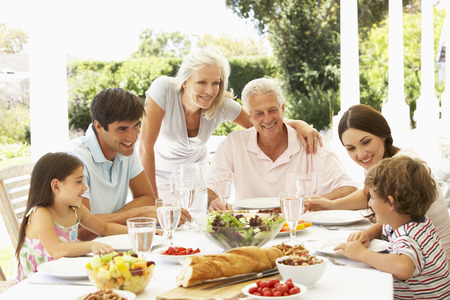 enjoy: Family eating lunch outside in garden