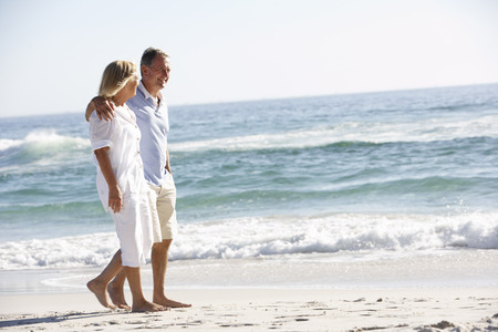 Senior Couple On Holiday Walking Along Sandy Beach Banque d'images