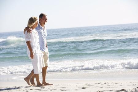 Senior Couple On Holiday Walking Along Sandy Beach Foto de archivo