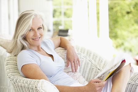 woman happy: Senior Woman Sitting Outside Reading Magazine Stock Photo