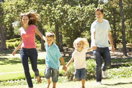 Family Running Towards Camera In Summer Park