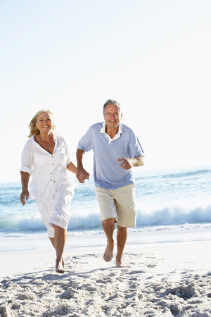 ancianos caminando: Pareja mayor ejecuta a lo largo de la playa
