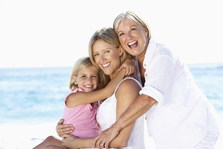 Grand-mère avec sa fille et petite-fille enlacés sur la plage de vacances Banque d'images