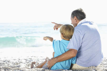 7 year old boys: Grandfather And Grandson Sitting On Beach Together On Holiday Stock Photo