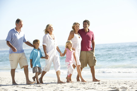 active family: Three Generation Family On Holiday Walking On Beach Stock Photo