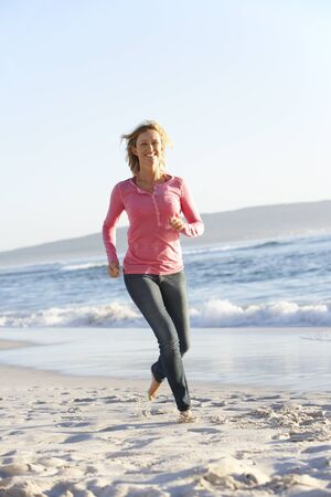 mid thirties: Young Woman Running Along Sandy Beach On Holiday