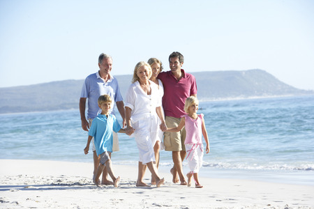 seaside: Three Generation Family On Holiday Walking On Beach Stock Photo