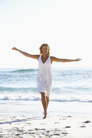 causal: Young Woman Running Along Beach Stock Photo