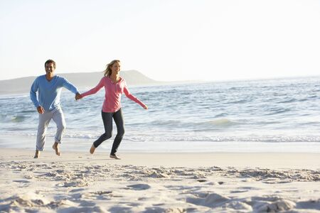 causal clothing: Young Couple Having Fun On Sandy Beach