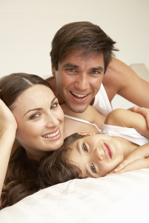 a young family: Young Family Relaxing On Bed Stock Photo