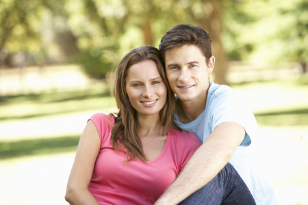 couple relaxing: Young Couple Relaxing In Park Stock Photo