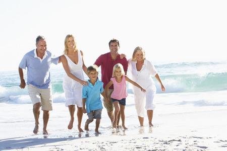 Three Generation Family On Holiday Running Along Beach Stockfoto