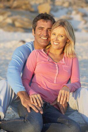mid thirties: Portrait Of Couple Sitting On Beach Stock Photo