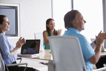 applauding: Business people Applauding Colleague In Boardroom Stock Photo
