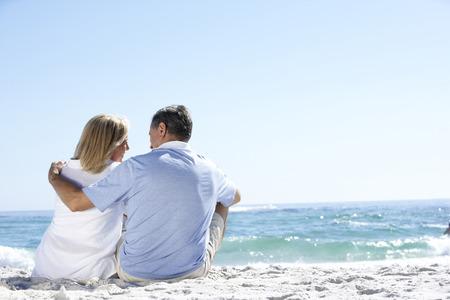 Senior koppel op vakantie sitting on zand strand