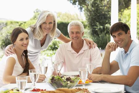 50s adult: Parents and Adult Children enjoying Al Fresco Meal Stock Photo
