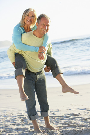 Senior Couple On Holiday With Husband Giving Wife Piggyback Stock fotó