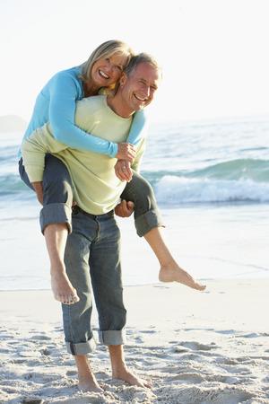 Senior Couple Having Piggy Bck On Sandy Beach Stock Photo