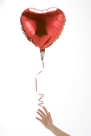 letting: Hand Letting Go Of Heart Shaped Balloon On White Background Stock Photo
