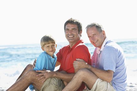 causal clothing: Grandfather With Grandson And Father Embracing On Beach Holiday