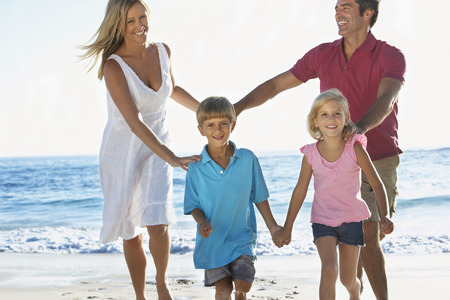 family beach: Young Family Running Along Sandy Beach On Holiday Stock Photo