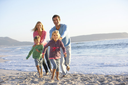 causal clothing: Young Family Running Along Sandy Beach On Holiday Stock Photo