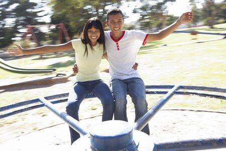 pareja adolescente: Pareja de adolescentes que se divierten en cruce giratorio Foto de archivo