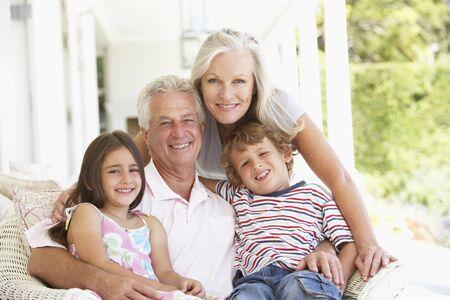 grandchildren: Grandparents Sitting Outisde with Grandchildren Stock Photo
