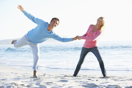 causal clothing: Young Couple Having Fun On Sandy Beach On Holiday Stock Photo