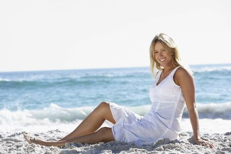 causal clothing: Young Woman Sitting On Sandy Beach
