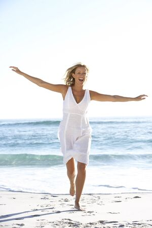 causal clothing: Casually Dressed  Young Woman Running Along Beach
