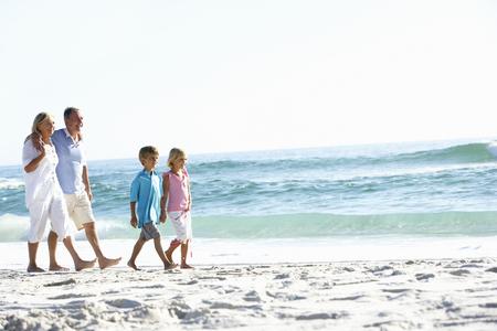 grandddaughter: Grandparents and Grandchildren Walking Along Beach