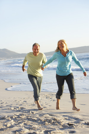 senior female: Senior Couple Walking Along Beach