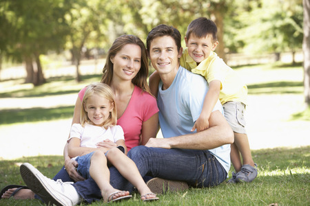 a young family: Young Family Sitting in Park Stock Photo