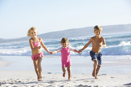 7 year old boys: Group Of Children Running Along Beach In Swimwear