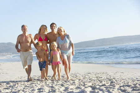 grandddaughter: Extended Family Walking Along Sandy Beach By Sea Stock Photo