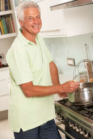 home cooking: Senior Man Preparing Meal At Cooker