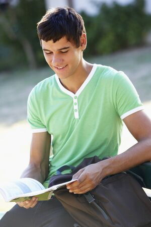 textbook: Male College Student Sitting On Bench Reading Textbook