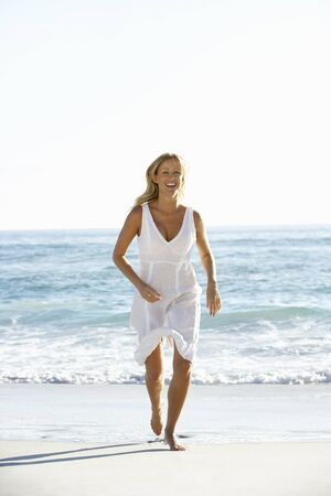 casually dressed: Casually Dressed  Young Woman Running Along Beach