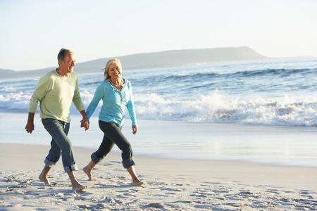 parejas caminando: Pares mayores que recorren a lo largo de la playa
