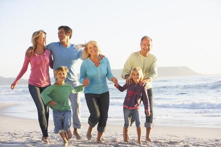 Famiglia delle tre generazioni in vacanza che funziona lungo la spiaggia