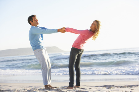 mid thirties: Young Couple Having Fun On Sandy Beach