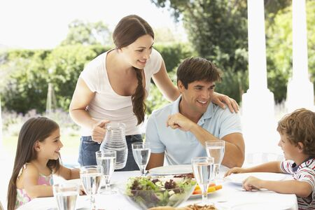 adult sandwich: Family Enjoying Outdoor Meal In Garden Together Stock Photo