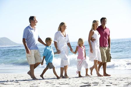 Drie-generatie familie wandelen langs zand strand