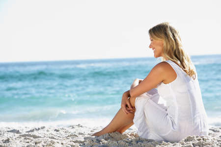 white woman: Young Woman Sitting On Sandy Beach