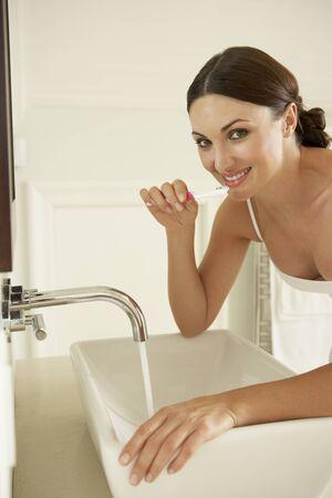 hygeine: Young Woman Brushing Teeth In Bathroom