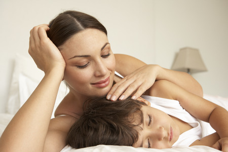comforting: Mother Comforting Sleeping Son In Bed Stock Photo