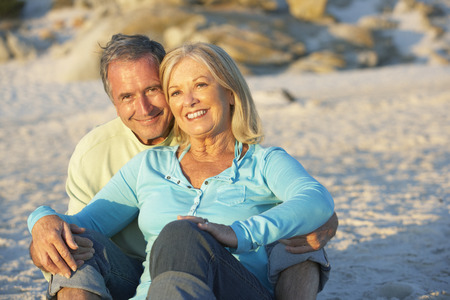 romantic beach: Senior Couple On Holiday Sitting On Sandy Beach