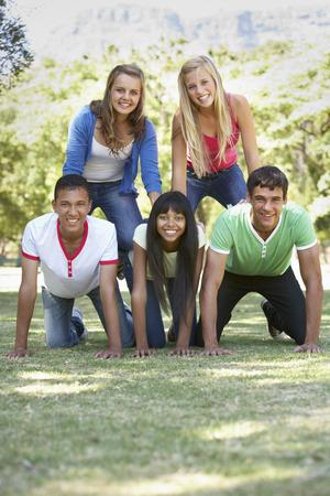 piramide humana: Grupo de amigos adolescentes que se divierten en el parque